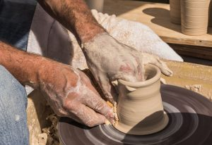 Pottery cup being formed on pottery wheel at Cary Farmers' Fall Festival
