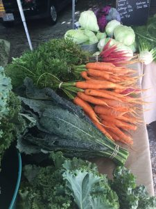 Carrots and kale on market table
